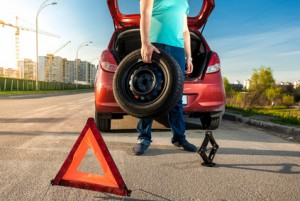 man holding spare wheel against broken car